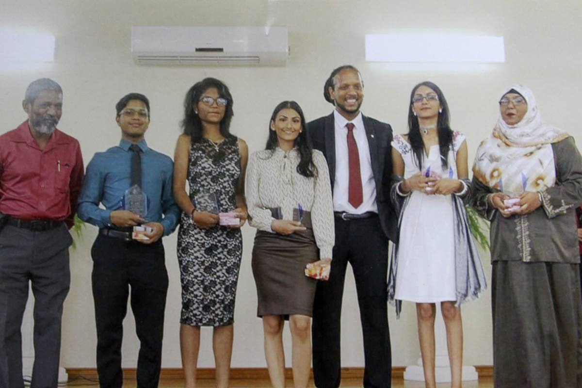 St George's College principal James Sammy (left to right, scholarship winners Adam Ali, Shania Caitlin Chadee, Azanna Mohammed, Abigail Ramlal and Rehanna Ali with past student chef Hassan De Four at the school's awards ceremony, St Mary's Anglican Church Parish Hall, Tacarigua on November 17. Absent are Megan Lawrence and Jewel Mulrain.