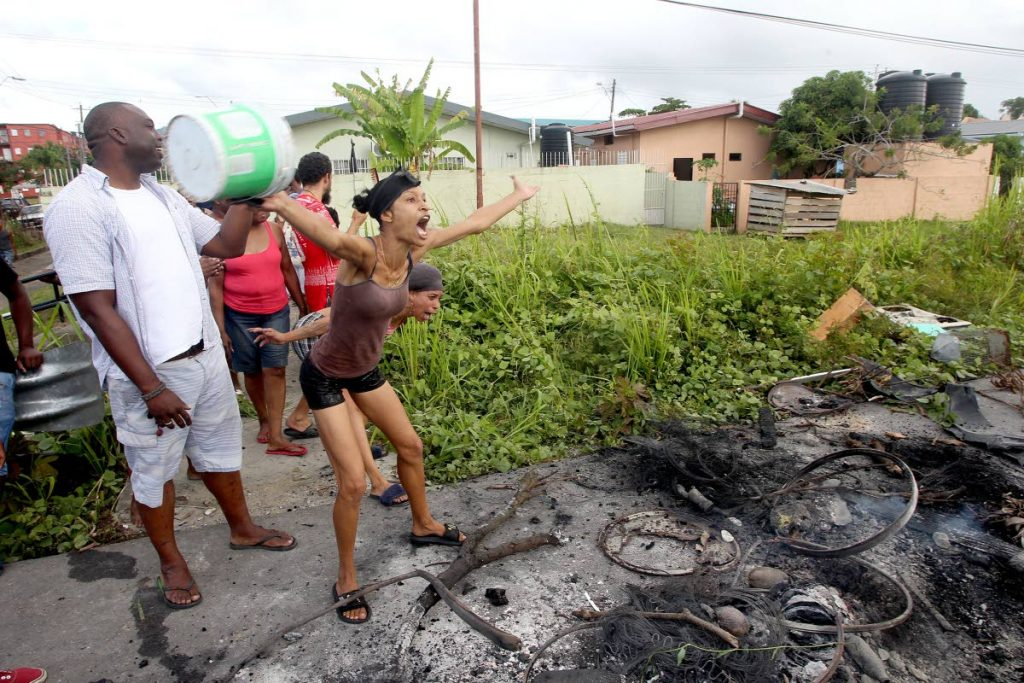 We want waaaater!: Two women vent their frustration over a lack of water in Maloney Gardens yesterday after a protest where debris was set on fire and scattered across Churchill Roosevelt Highway yesterday. Photo by Lincoln Holder