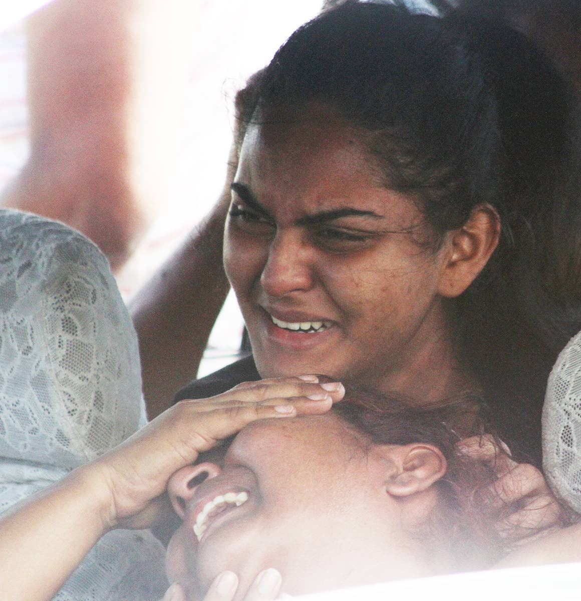 SUNDAY SORROW:Shivana Roodal, top, consoles her weeping mother Maltie yesterday after the body of Shivana's father and Maltie's husband Pooran Roodal was found in his car with a stab wound to his neck in Kelly Village, Caroni.