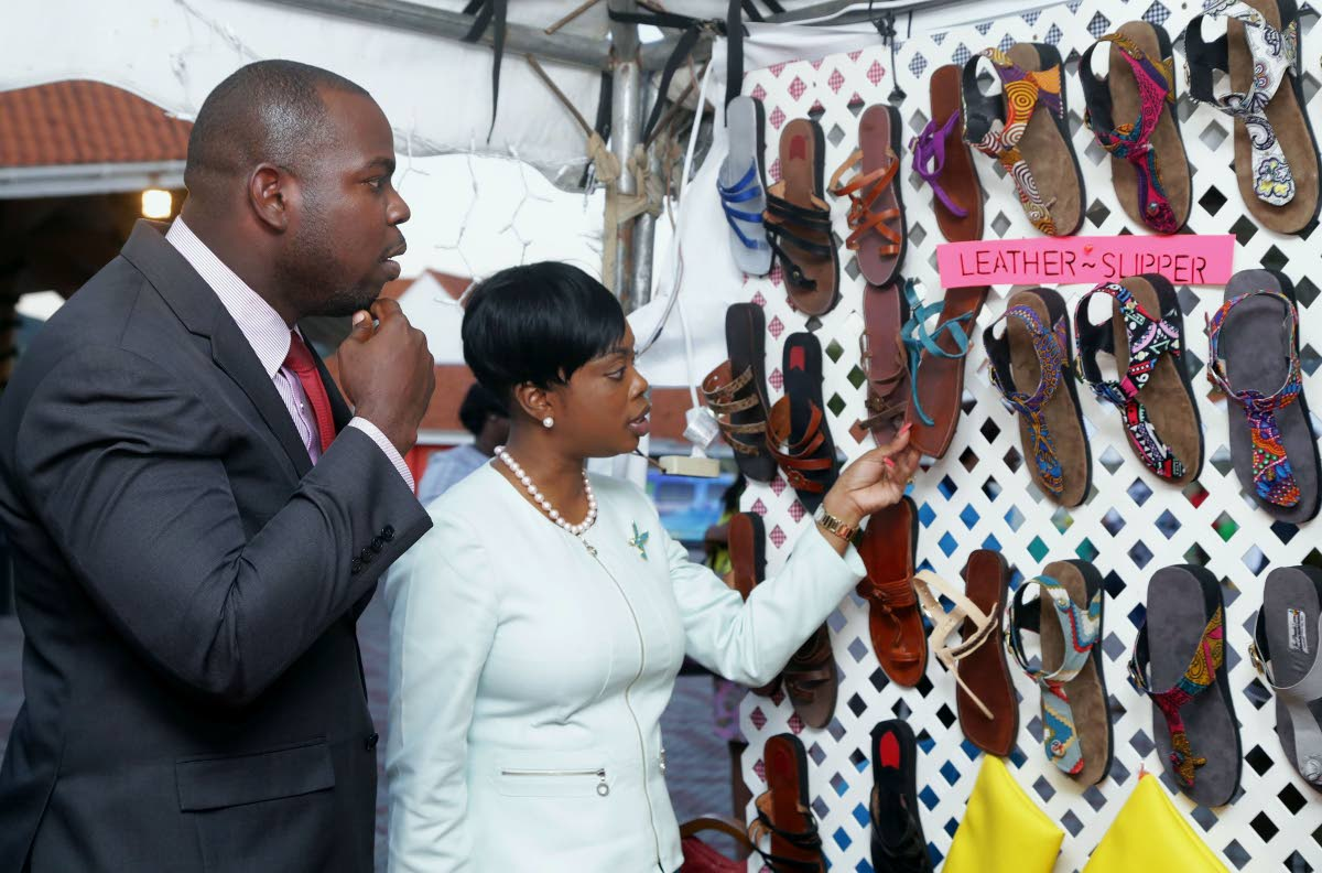 Tourism Secretary Nadine Stewart-Phillips, right, and Assistant Secretary of Community Development Shomari Hector, look at hand-crafted sandals on display at a booth at the Christmas Village on the Milford Road Esplanade last week.