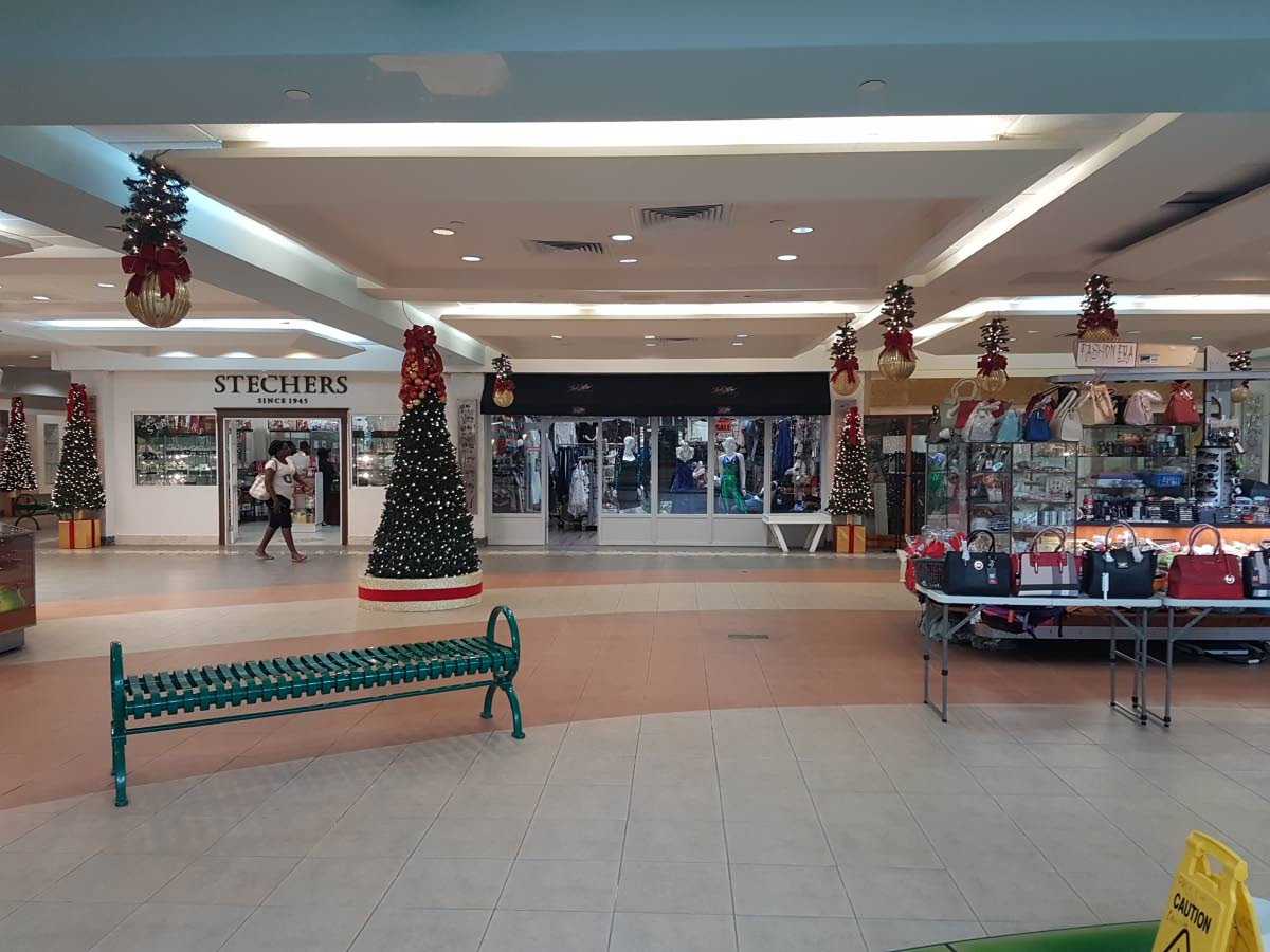 In the distance, a shopper walks along mostly empty corridors, and shops, of the Gulf City Mall on Saturday at midday.