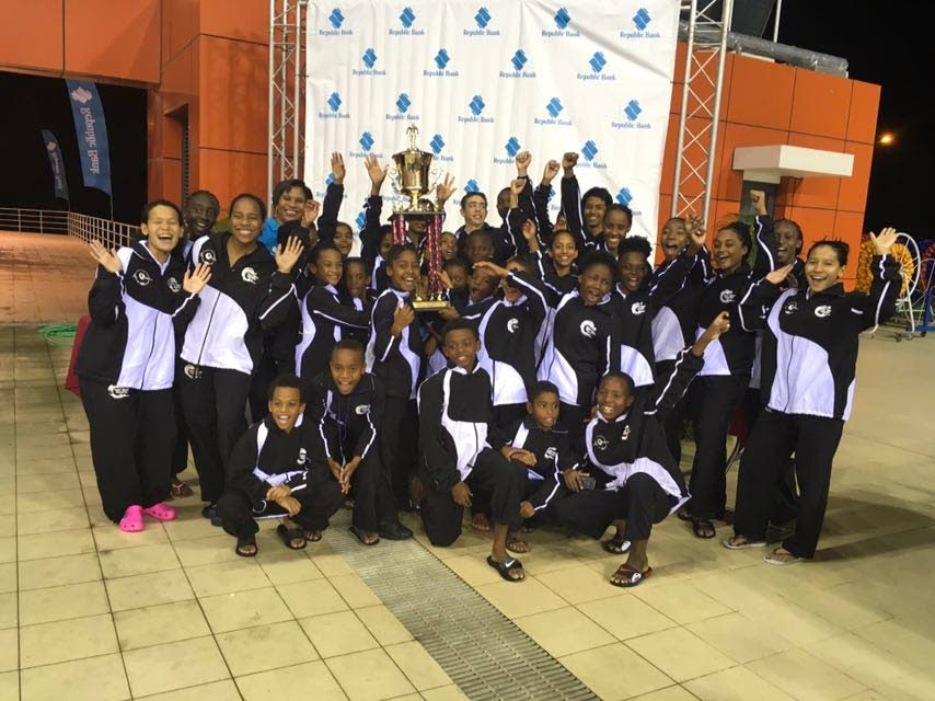 CHAMPS: Members of Tidal Wave Aquatics celebrate winning the overall title at the ASATT Invitational Meet on Sunday at the National Aquatic Centre, Couva.