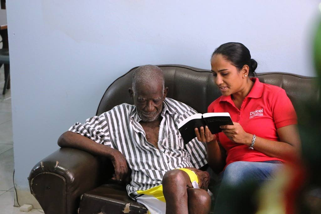 Digicel Foundation project coordinator, Diana Mathura-Hobson, right, reads a Psalm to this man.