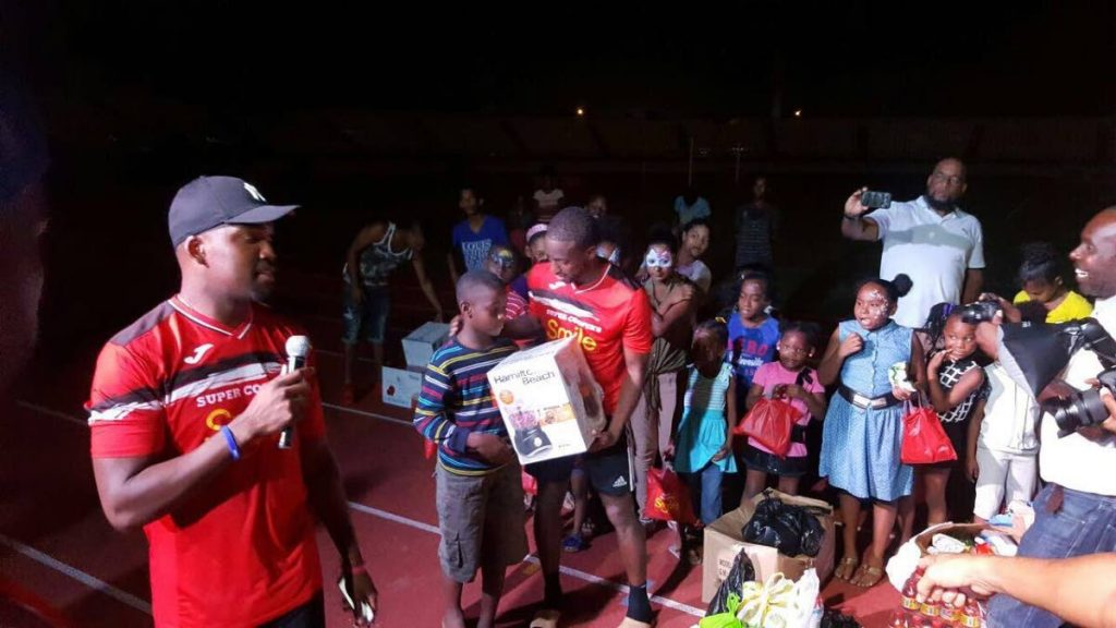 National footballer Kevin Molino gives a package to a child at the Super Cooper Smile Charity Event at the George Boyce Recreation Ground in Arima, on Sunday. TT and West Indies cricketer Darren Bravo, left, helps coordinate the distribution of gifts.
