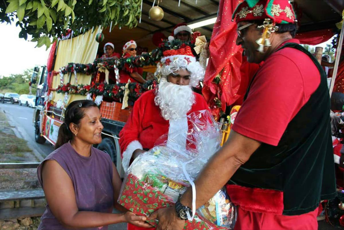 FOR YOU: Alexis Sieunarine, dressed as Santa Claus, looks on as a helper gives a woman a Christmas hamper. Sieunarine and his father businessman Allan Sieunarine were behind an initiative which saw over 4,000 hampers being given to needy children during the Christmas Season.
