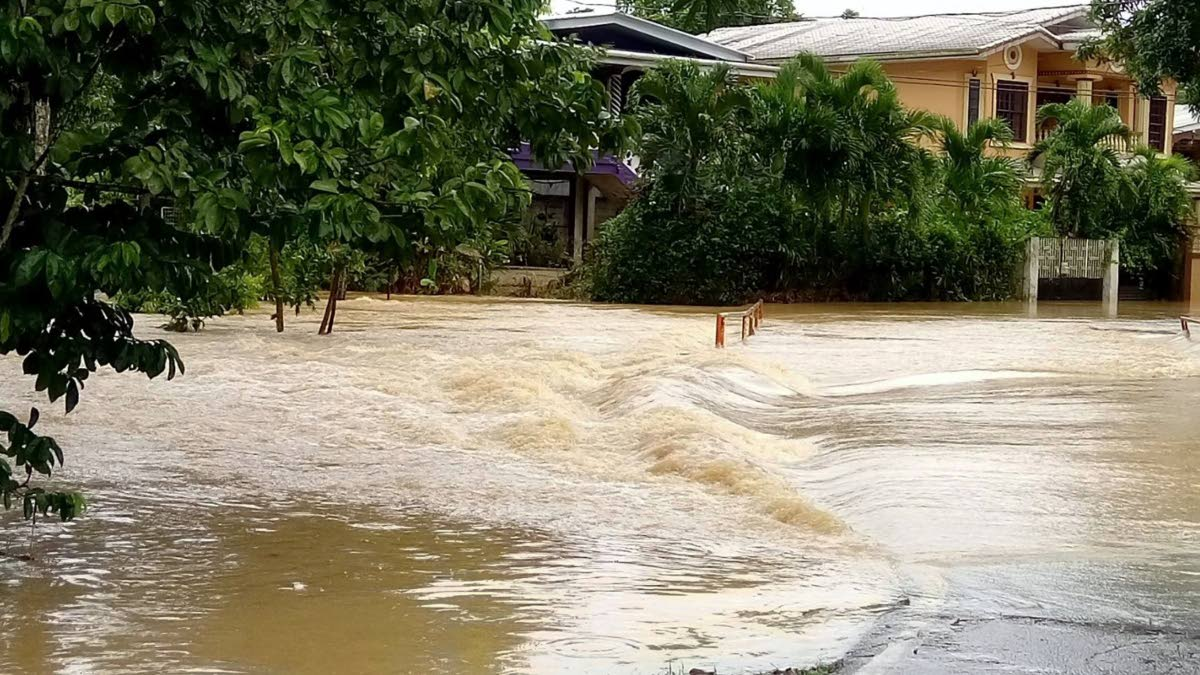 FLOODED: Flood water covers Kent Street in Williamsville yesterday following hours of almost continuous rainfall since Wednesday. The photo, taken by Vicky Kissoondath, was posted on the TTWeatherCenter's facebook page.