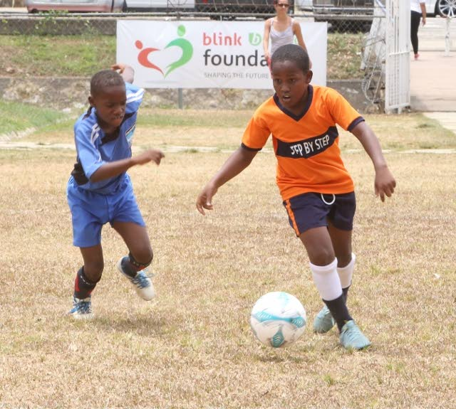 A young footballer from Step by Step, right, makes a play during the Maylee Attin Johnson 3v 3 tournament last year. This year's edition of the tourney kicks off today at the Hasely Crawford Training Grounds, Port of Spain.