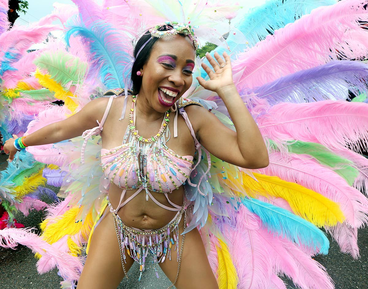 Carnival flashback: A masquerader savours the relvery with Large Band of the Year winner Ronnie and Caro on Carnival Tuesday last year. File photo