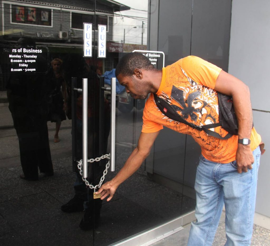CLOSED: An RBC Sangre Grande customer checks the lock on the door of the branch.