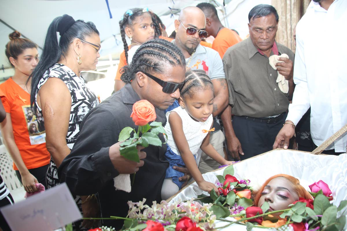 SHE'S GONE: Brian David holds his niece Irisa as she places a flower next to her mother Arisa David at the funeral held at Limehead Road, Chase Village yesterday.
