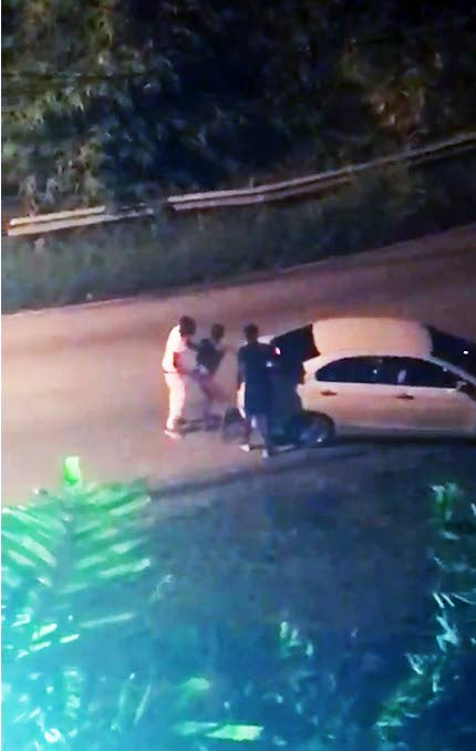 KIDNAPPED: This freeze frame taken from a video posted to social media shows Nicholas Juman, centre, being forced into the trunk of a car on Saturday night along Lady Young Road near the Trinidad Hilton. Juman later managed to escape.
