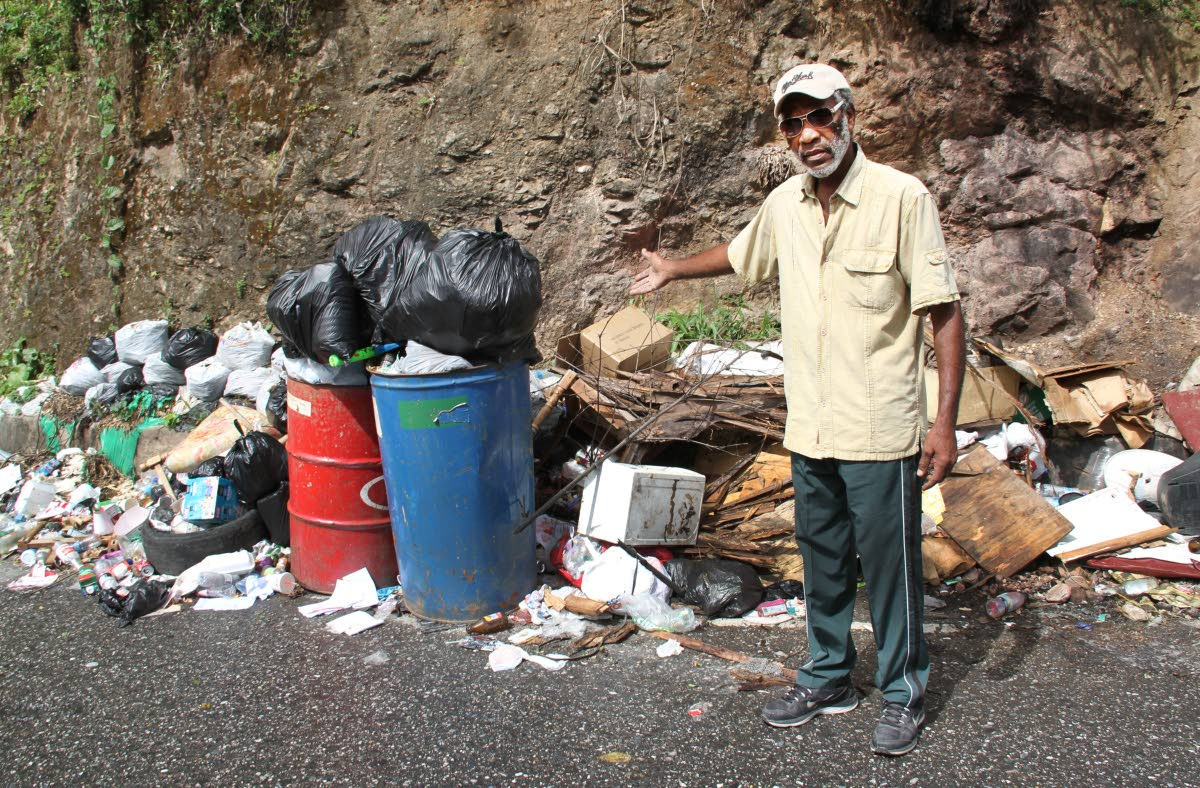 STINK SITUATION: Roland Augustus points to piles of garbage dumped along Morne Coco Road. PHOTO BY SUREASH CHOLAI