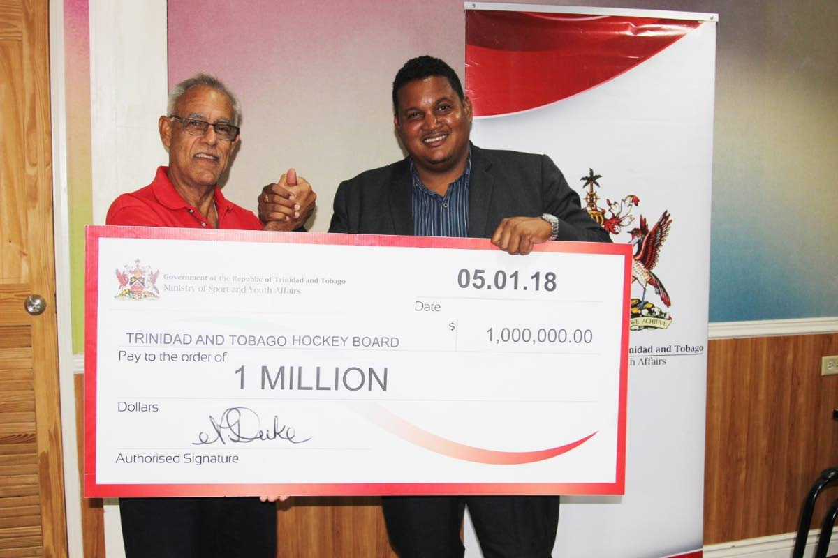 Minister of Sport and Youth Affairs Darryl Smith, right, presents  president of the Trinidad and Tobago Hockey Board Douglas Camacho with a cheque at the TT Olympic Committee head office, on Friday.