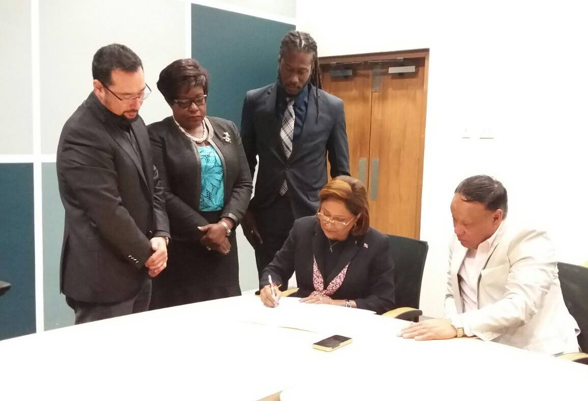 SIGNED: Opposition Leader Kamla Persad-Bissessar signs the document confirming the Opposition's support of Government's nominee for President, retired judge Paula Mae Weekes. Looking on from left are Govt MPs Stuart Young, Camille Robinson Regis and Adrian Leonce while seated at right is Opposition MP David Lee.