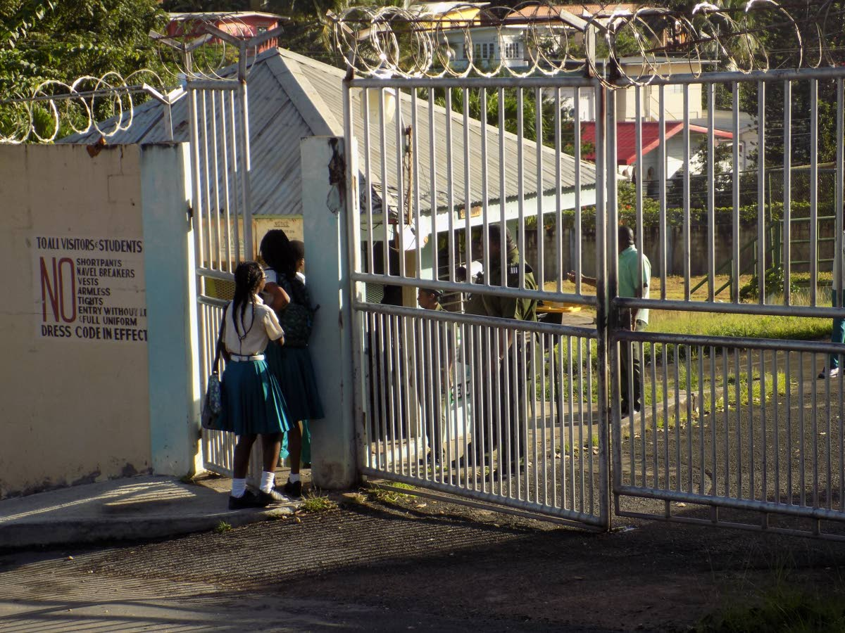 Students of the Morvant Laventille Secondary School arrive with their parents for class yesterday after form two student Joshua Andrews was killed in a taxi in Pelican Extension, Trou Macaque on Monday.
