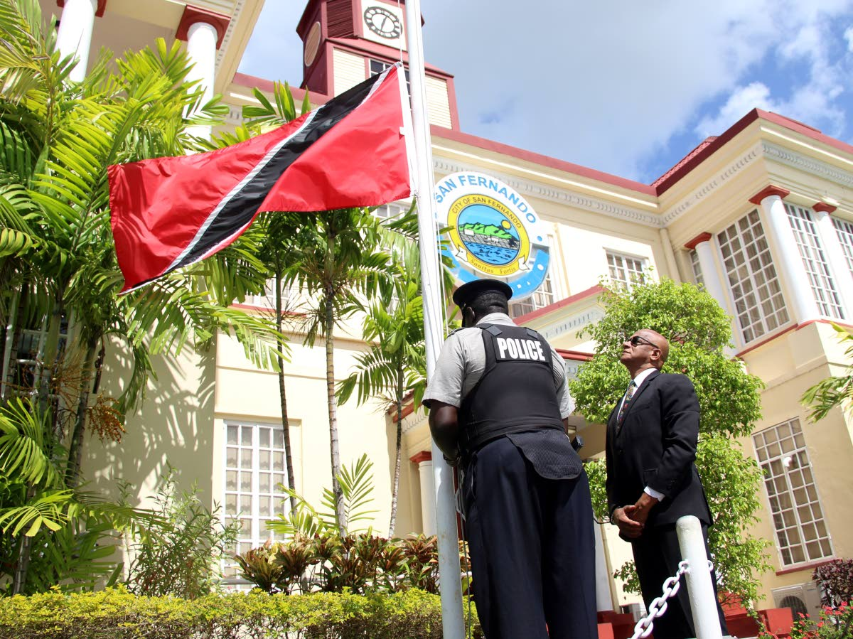 San Fernando Mayor Junia Regrello looks on as PC O'Neil Williams of the San Fernando City Police lower the national flag at the San Fernando City Corporation to half-mast yesterday to observe the death of former president George Maxwell Richards.