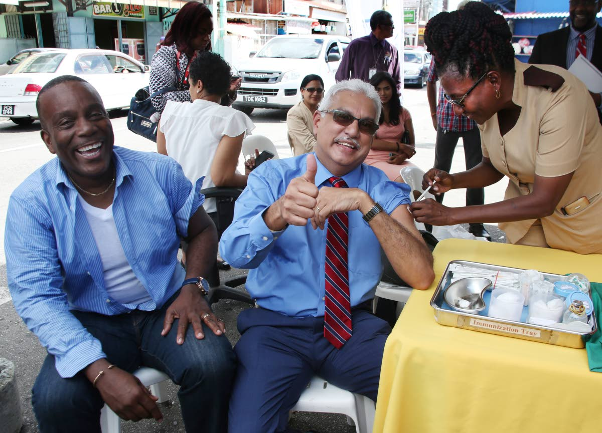NO CRY BABY HERE: Health Minister Terrence Deyalsingh puts on a brave face as he receives  his flu injection from nurse Marcia Thomas-Wilson at the Tunapuna market yesterday.  Lending  support is Tunapuna MP Esmond Forde.