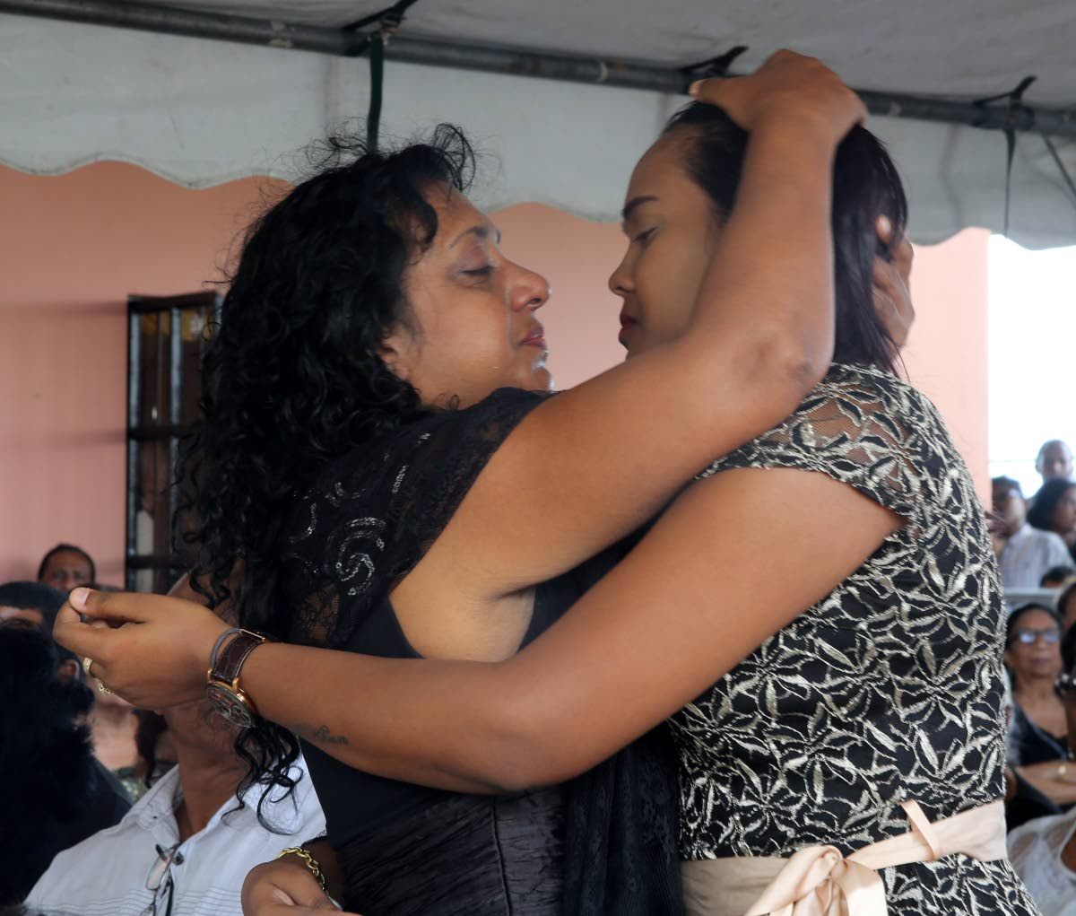 Murder victim Brandon Khan's mother Marilyn Khan (left) and his wife Krystal Chankar-Khan console each other at his funeral held at the family's Chase Village home yesterday.   PHOTO BY VASHTI SINGH