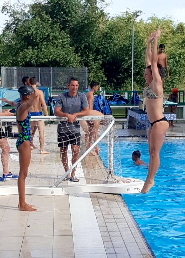 A Duke diver demonstrates to one of the young swimmers the proper technique on deck as coach Nunzio Esposto looks on.