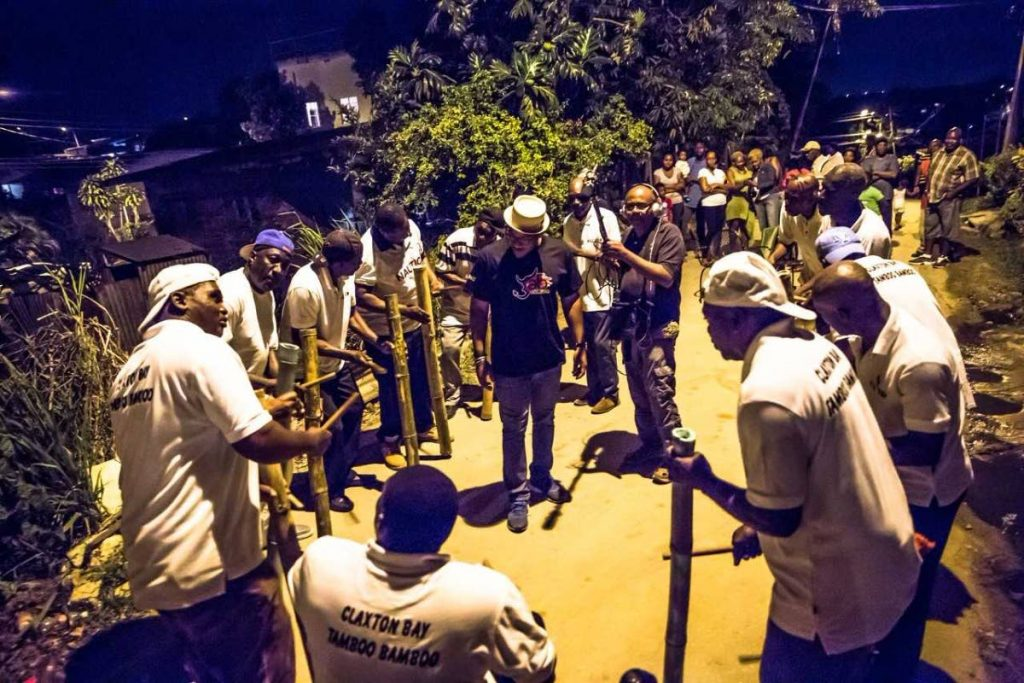 This photo by Maria Nunes was taken during the field recording of the Claxton Bay Tamboo Bamboo troupe. At centre are Etienne Charles (in hat) and sound engineer Robin Foster. PHOTO COURTESY MARIA NUNES.