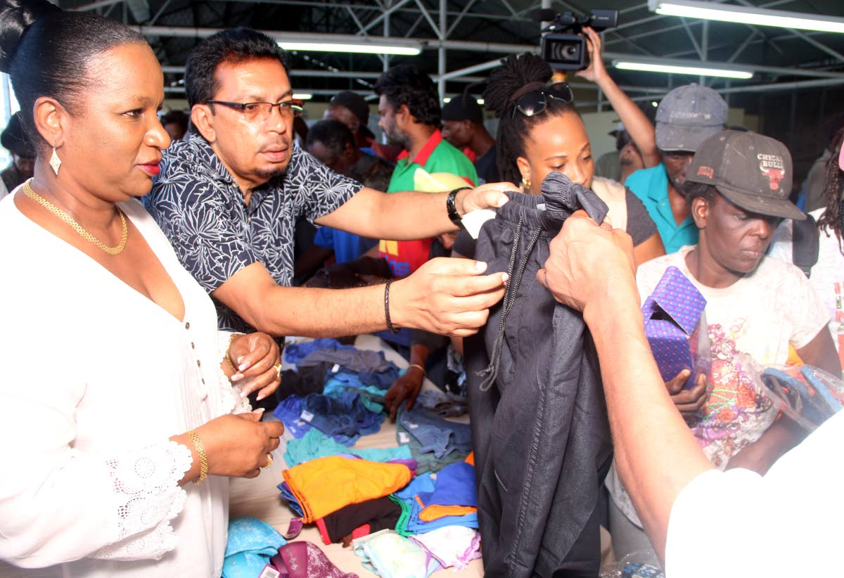 Minister of Social Development Cherrie-Ann Crichlow-Cockburn and Local Government Minister Kazim Hosein share items of clothing at the newly opened Centre for Displaced People in San Fernando yesterday.