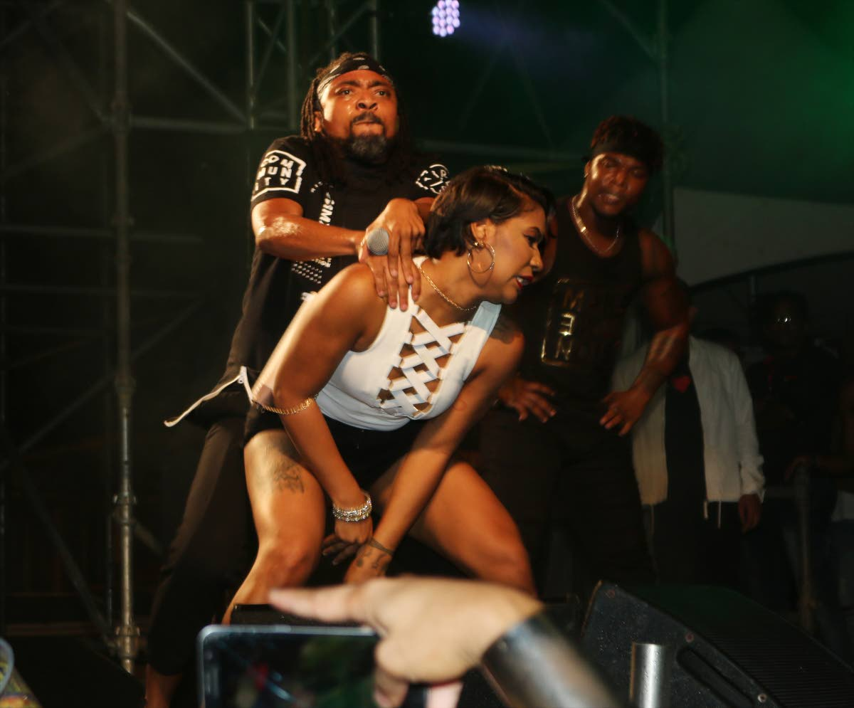 Machel Montano performs with a patron at Red Ants' Stumped fete on Saturday at the Queen's Park Oval. By the time the singer took to the stage, the fete's promoters were ordered reduce their sound levels.