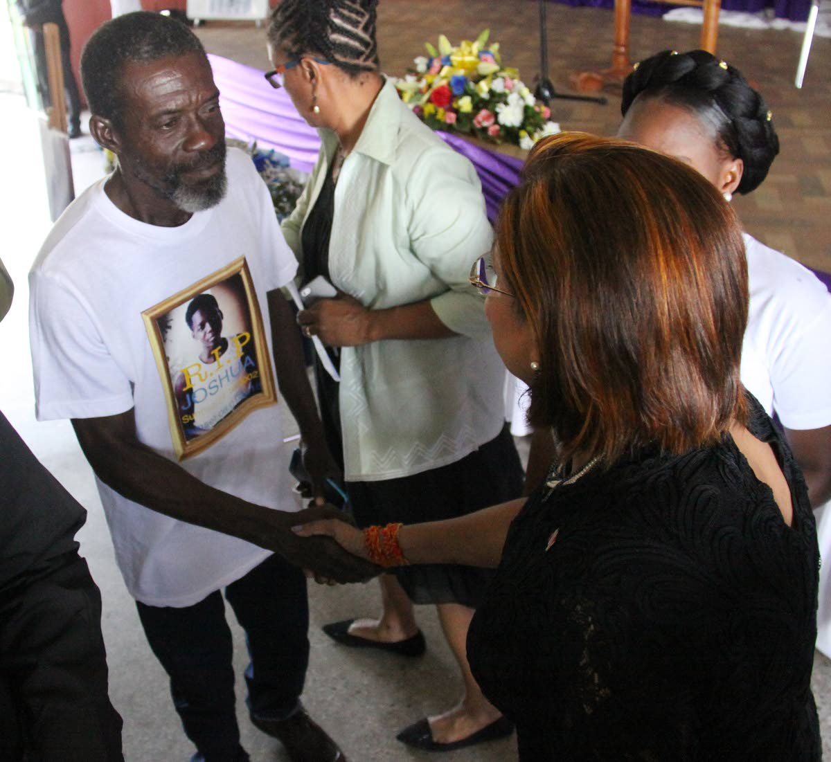 Opposition Leader Kamla Persad-Bissessar is greeted at the funeral of Joshua Andrews by his father Tony at the Transport and Industrial Workers Union hall, Eastern Main Roadm Laventille.