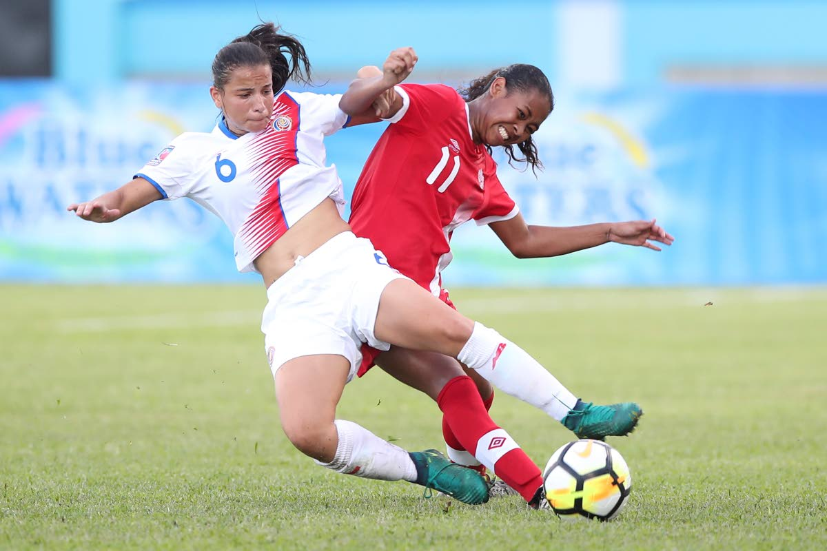 Costa Rican defender Maria Elizondo,left, is tackled by Canadian striker Jayde Riviere during action in the opening match of the CONCACAF U20 Women's Championships at the Ato Boldon Stadium, Couva yesterday. Canada won the match 3-1.