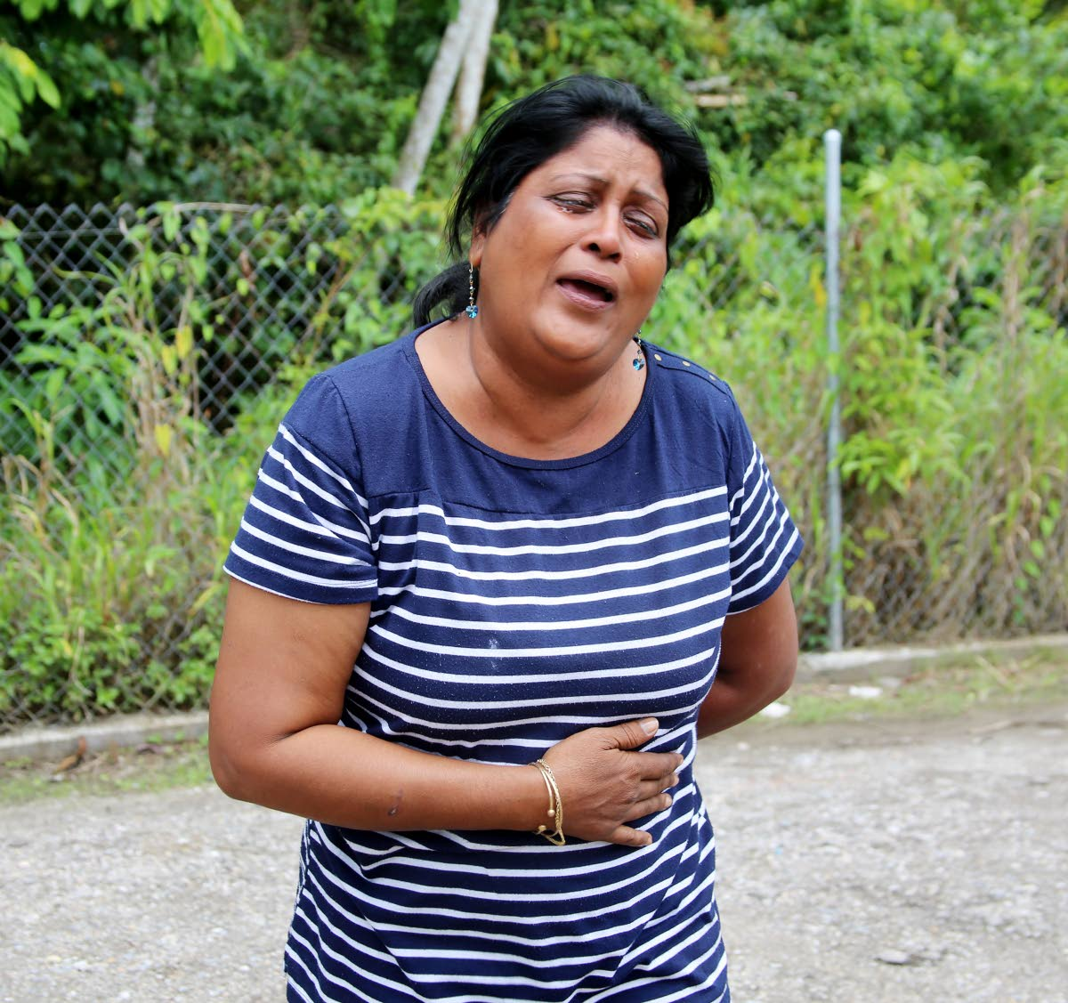 Nirmala Sieukaran weeps yesterday for a relative who is in police custody for questioning in the fatal stabbing of Dayanand  Dookie at Solomon Drive, Cunupia, on Friday.  Photo by Vashti Singh