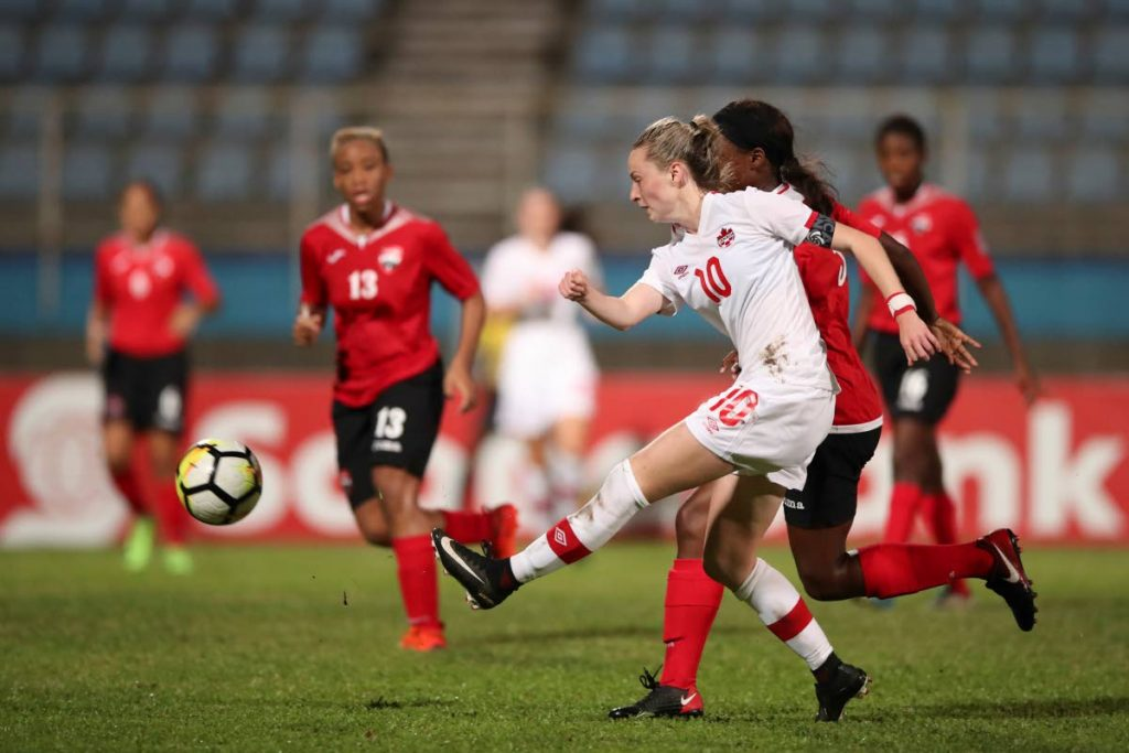 Canadian striker Gabrielle Carle takes a shot at goal against Trinidad and Tobago yesterday during action in the CONCACAF U20 Women's Championships at the Ato Boldon Stadium,Couva.