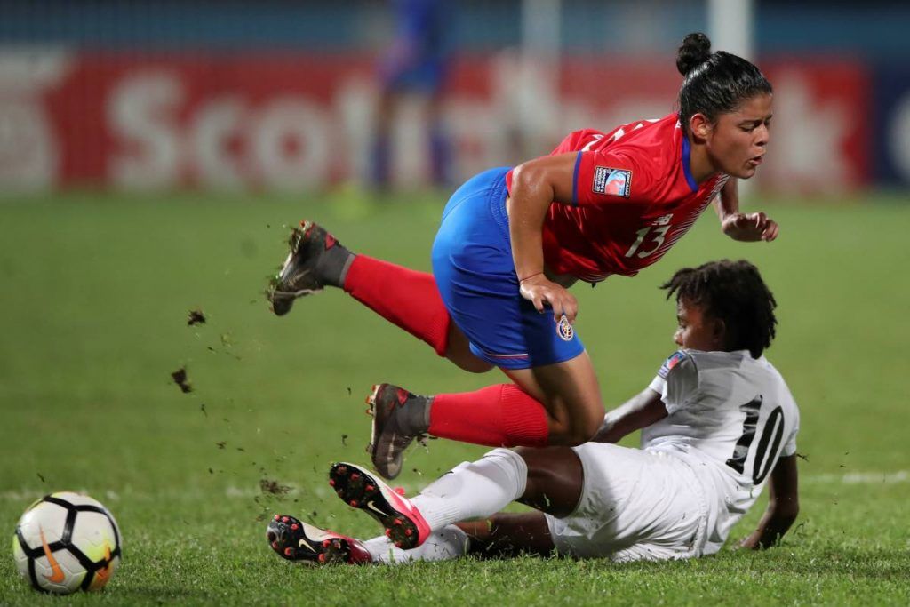 Costa Rica's Cristel Sandi is slide tackled by TT's Aaliyah Prince (10) yesterday in their CONCACAF Women's U20 match at the Ato Boldon Stadium, Couva.