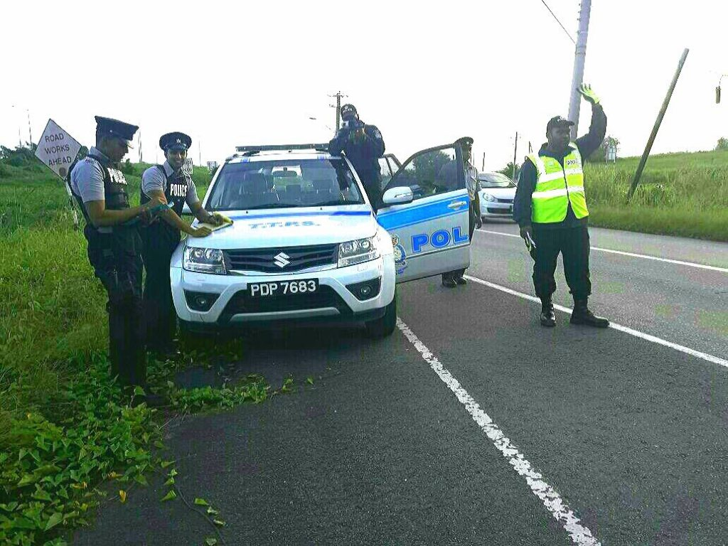 SPEED TRAP: Police officers on a speed-trap traffic exercise along south Trunk Road, La Romaine