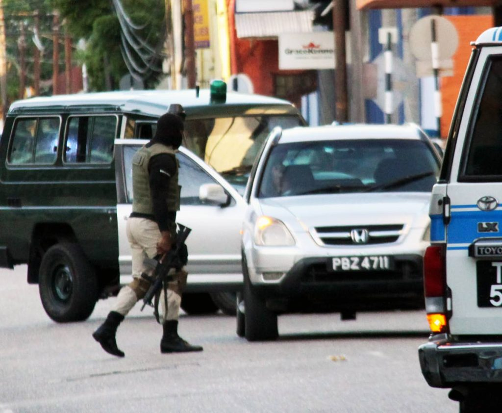 ANOTHER GONE: A prison officers walks in front of the car in which his colleague Davindra Babooram was shot dead on Frederick Street, Port of Spain shortly after leaving work at the prison.   PHOTO BY ANGELO M MARCELLE