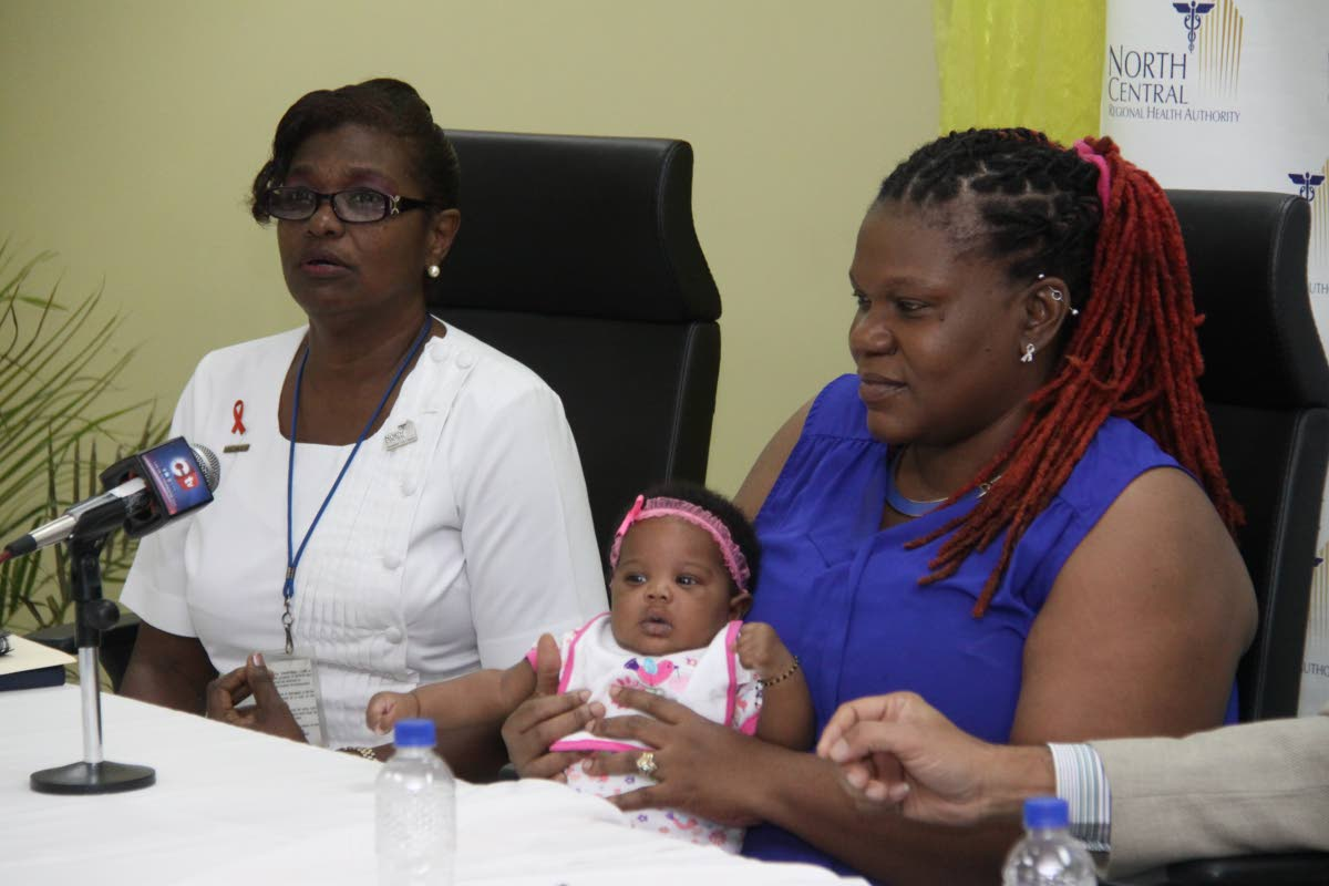 A nurse's care: A midwife sits alongside Roxanne Applewhite and her baby girl Imani during the launch of the NCRHA post natal home care programme on January 21.