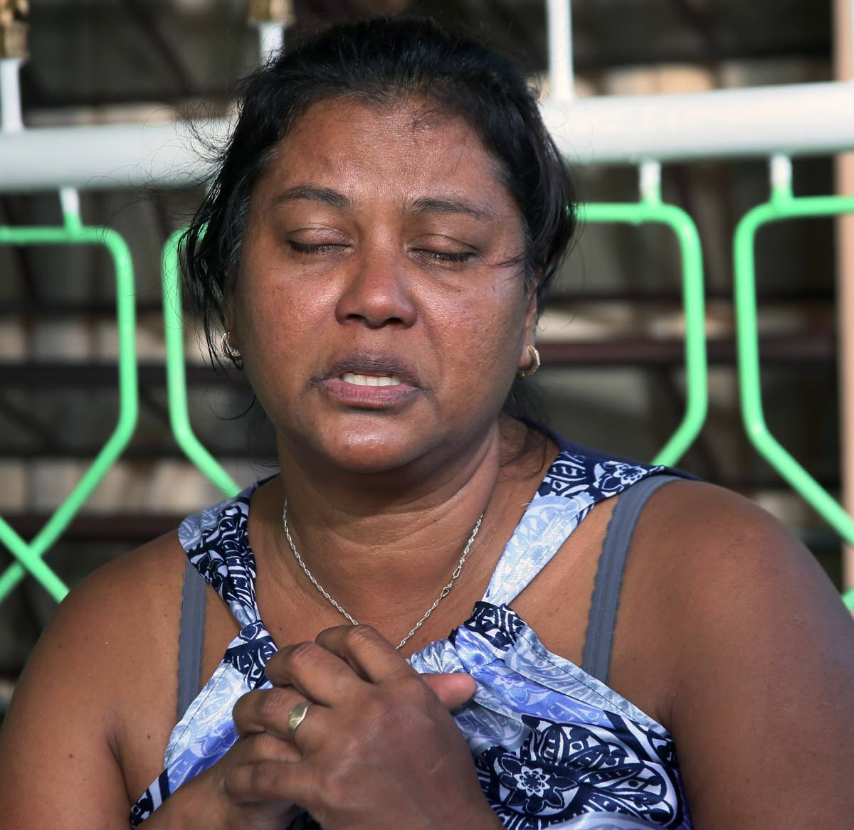 Wife's Pain: Asha Boodooram, the wife of murdered Prisons Officer Devendra  Boodooram, clutches her hands close to her heart telling Newsday how much it pains her heart following the senseless murder of her husband. Boodram was the father of two girls. PHOTO BY AZLAN MOHAMMED]