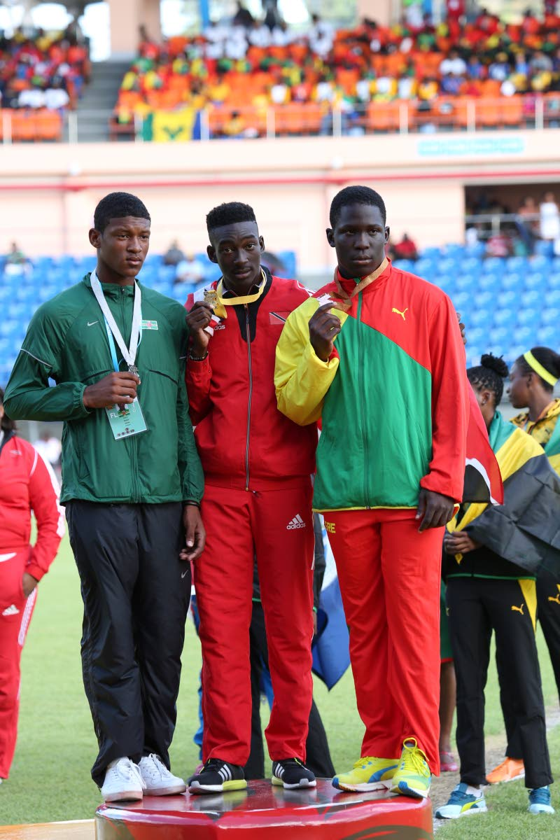 ZENITH CHAMP: In this March 2016 file photo, Tobago's Zenith javelin champion Tyriq Horsford, centre, shows off his gold medal won in the Boys Under-18 category at CARIFTA Games in Grenada.