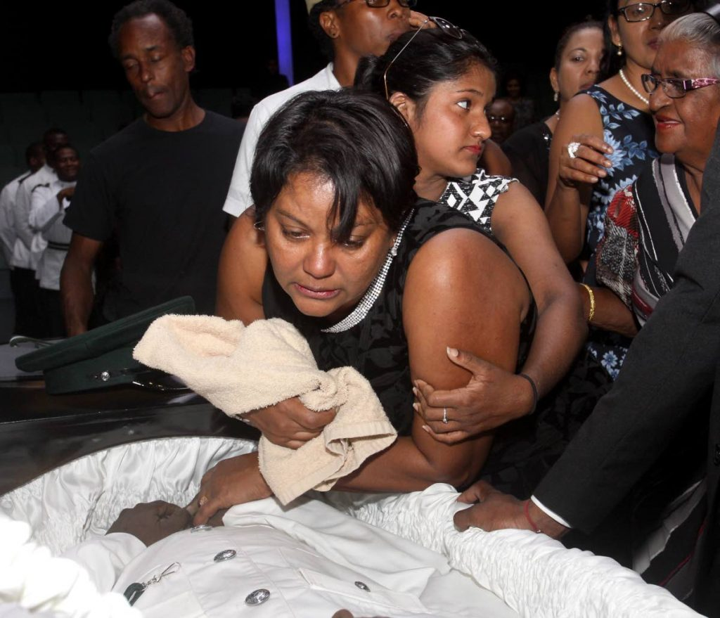 Asha Boodooram, wife of murdered prison officer Devendra Boodooram, weeps over his body at his funeral held at the Faith Assembly International in Arouca.