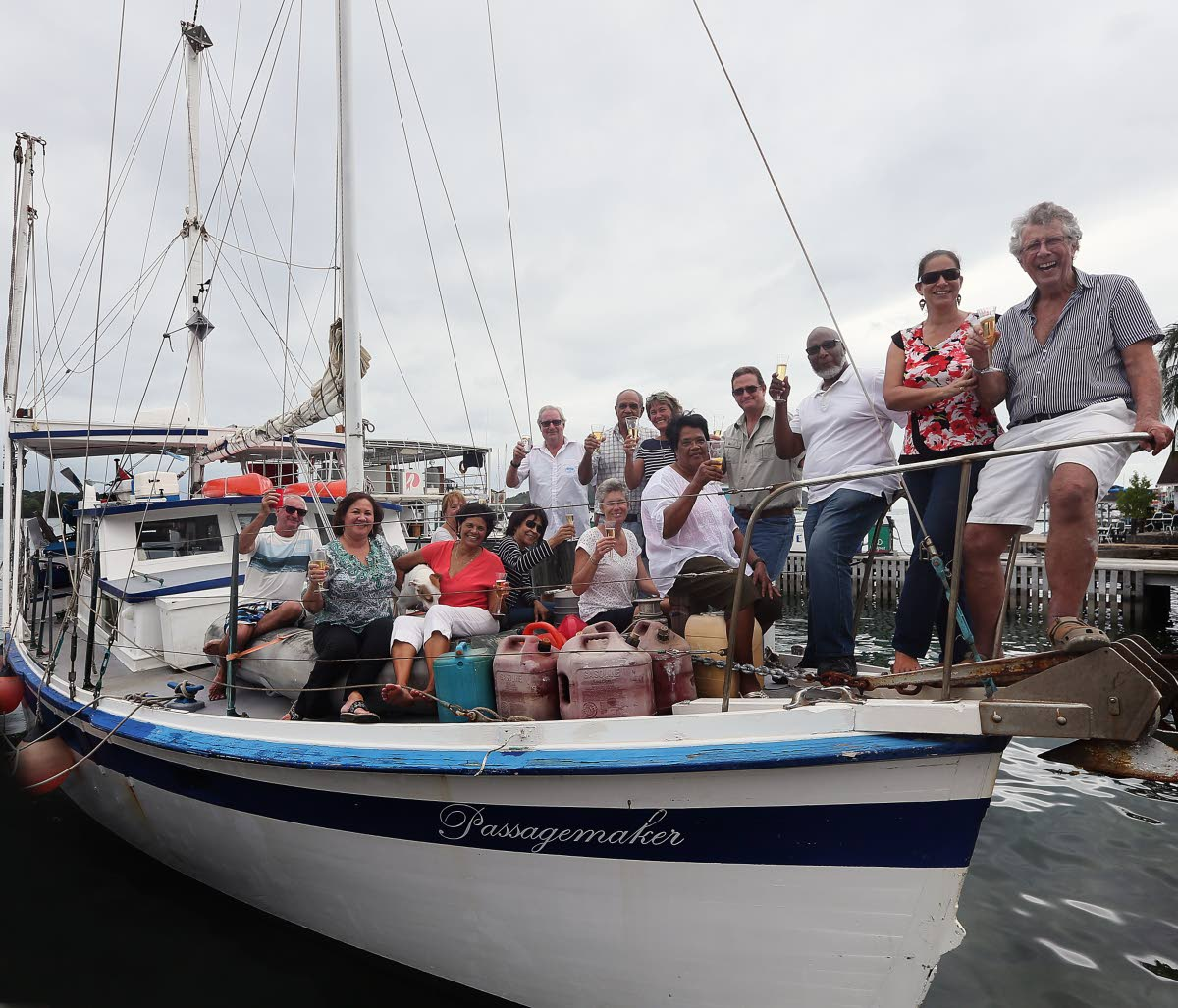 Sea conquerer: Adventurer Peter Quentrall-Thomas celebrates aboard the Passagemaker in Chaguaramas on Friday with his wife and friends after sailing across the Atlantic Ocean.