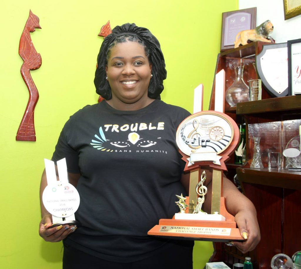 Arranger Vanessa Alexandra Headley proudly displays the trophies won by Small Band Panorama champion Golden Hands, with her song Trouble, at the band's panyard, Independence Avenue, San Fernando yesterday.