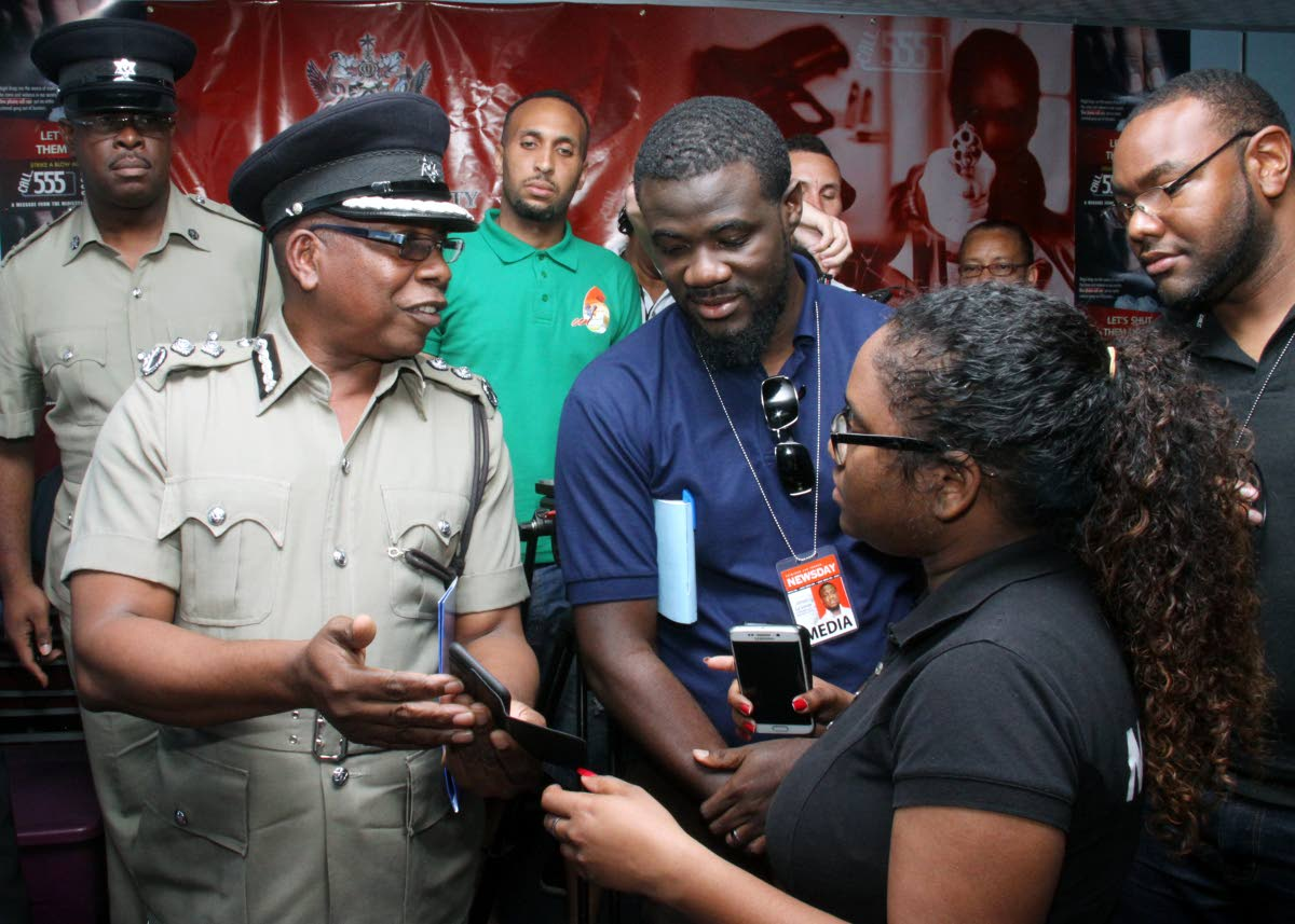 Top cop info: Acting Police Commissioner Stephen Williams shows reporters images of a man killed in a shootout with an officer in Arima yesterday at Police Administration Building, Port of Spain. Williams earlier said the Carnival threat is still alive. Photo by Angelo Marcelle