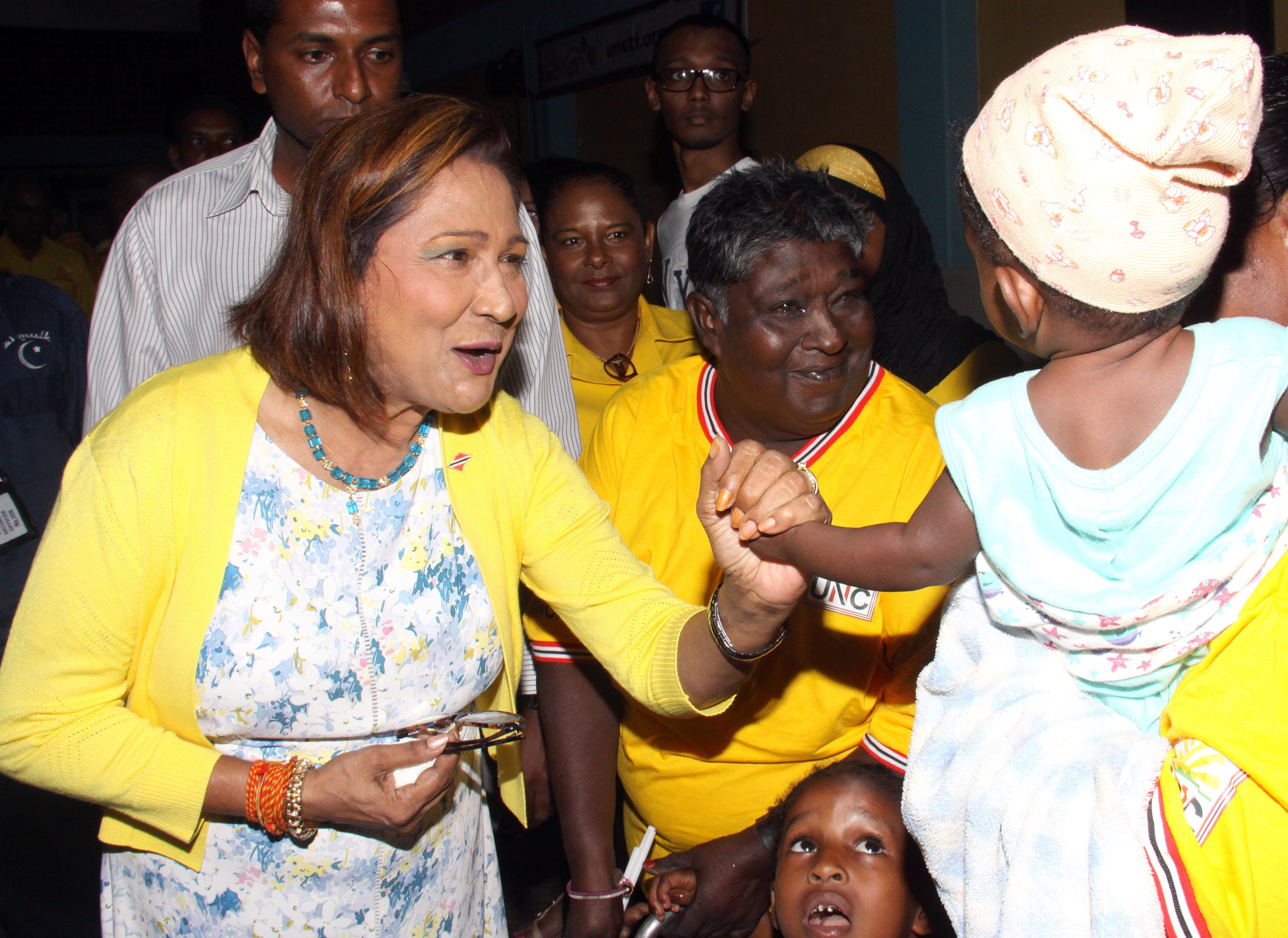 TELL MAMMY VOTE FOR ME: Opposition Leader Kamla Persad-Bissessar plays with a baby as she arrived at the UNC's Monday Night Forum at the St Joseph Secondary School.  PHOTO BY ANGELO MARCELLE