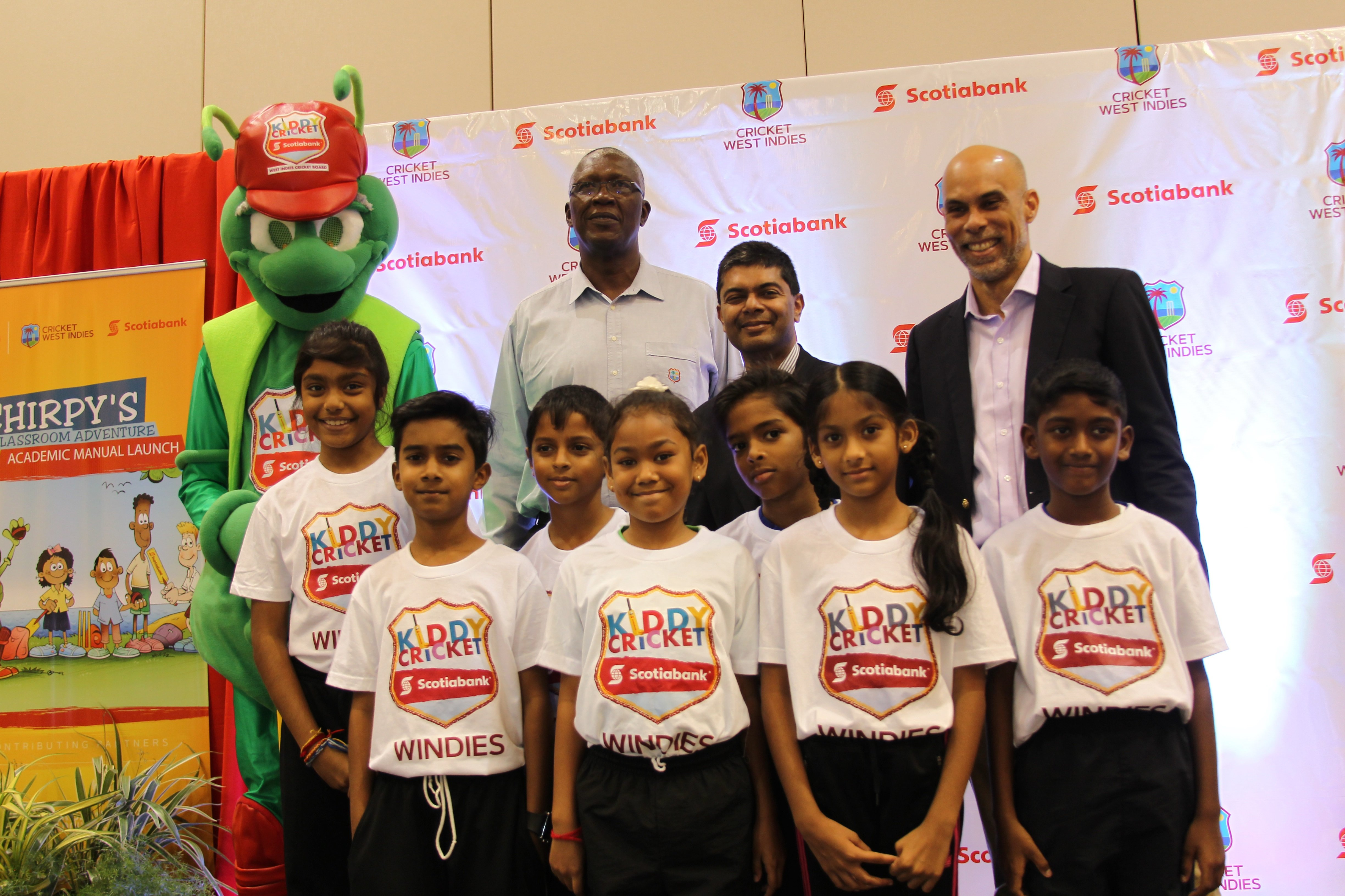 (Back row left to right) Kiddy Cricket mascot Chirpy; former West Indies player Joel Garner, CWI ambassador; Reshard Mohammed, Scotiabank VP; and director of cricket at CWI, former West Indies player Jimmy Adams pose with youngsters yesterday at the launch of Scotia's Kiddy Cricket Academic Manual at the Hyatt Regency, PoS. PHOTO BY RATTAN JADOO