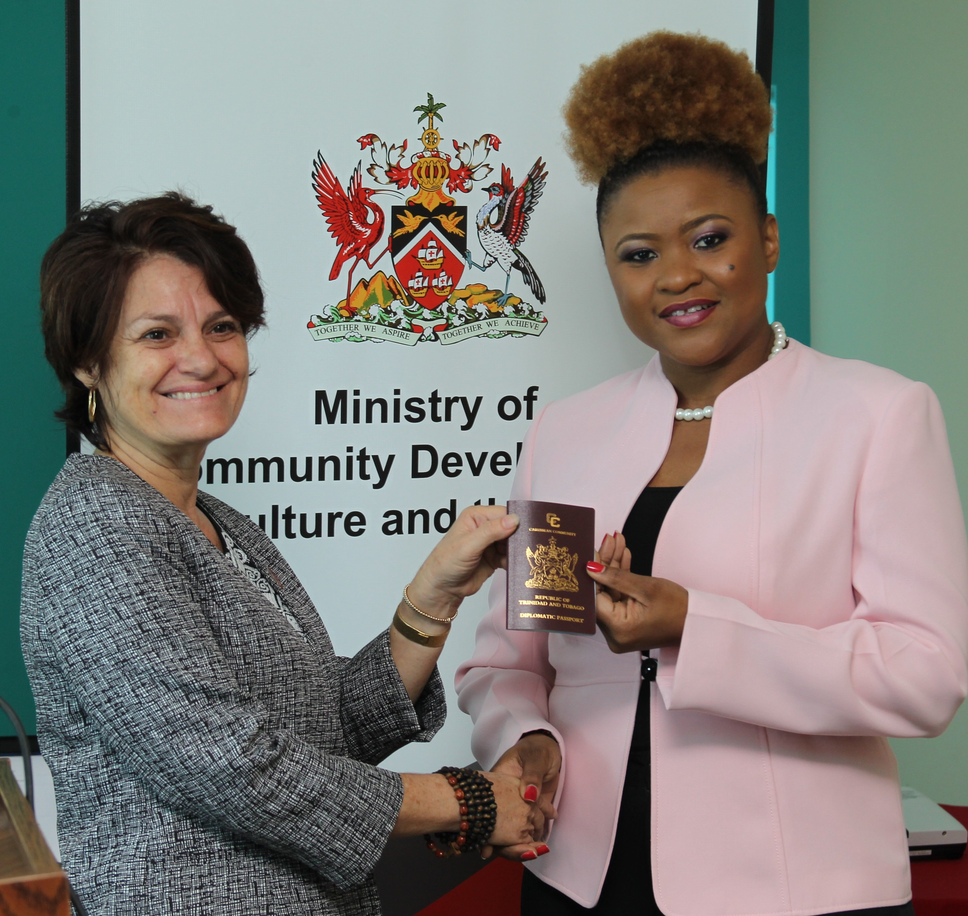Lorraine O'Connor (left) receives the diplomatic passport on behalf of Calypso Rose from Culture Minister Dr Nyan Gadsby-Dolly.