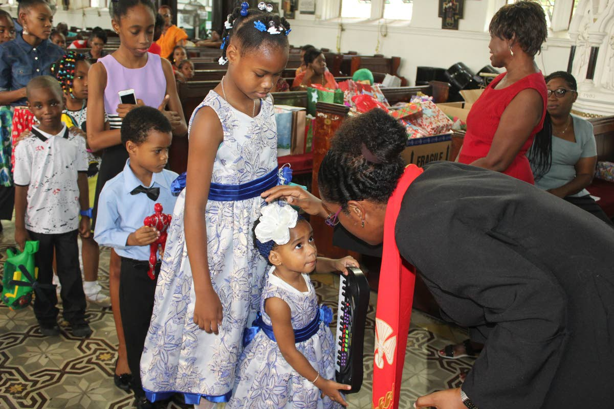 Blessed are the children: Anglican priest Shelley Ann Tenia blesses children and their toys at the Feast of the Holy Innocents service, Holy Trinity Cathedral, Port of Spain on December 28, 2017. File photo