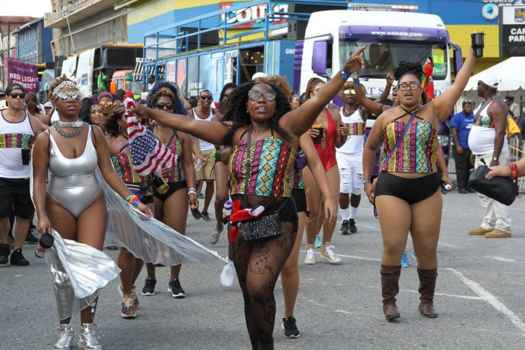 Masqueraders move through the streets on Carnival Monday.