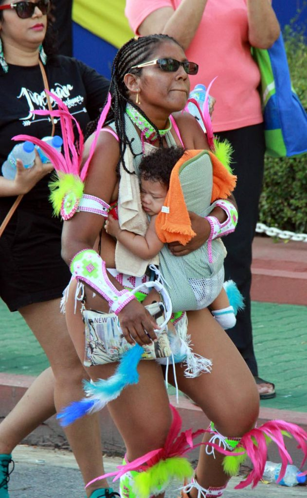 HAVING A GOOD TIME: This woman is seen playing mas in San Fernando on Carnival Monday with a baby strapped to her chest. She was warned by police and band officials to give the baby to someone else.