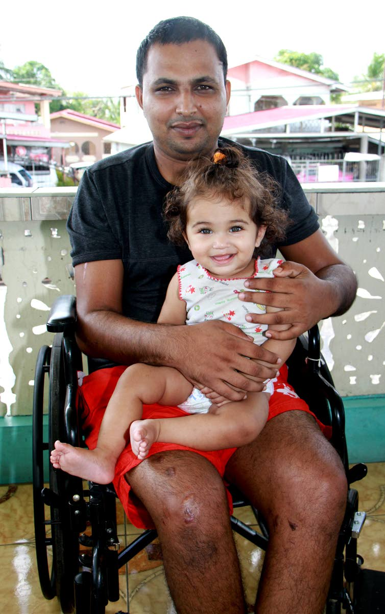 SEEKING JUSTICE: Shameer Boban with his daugher Karen, eight months, at their Barrackpore home yesterday.