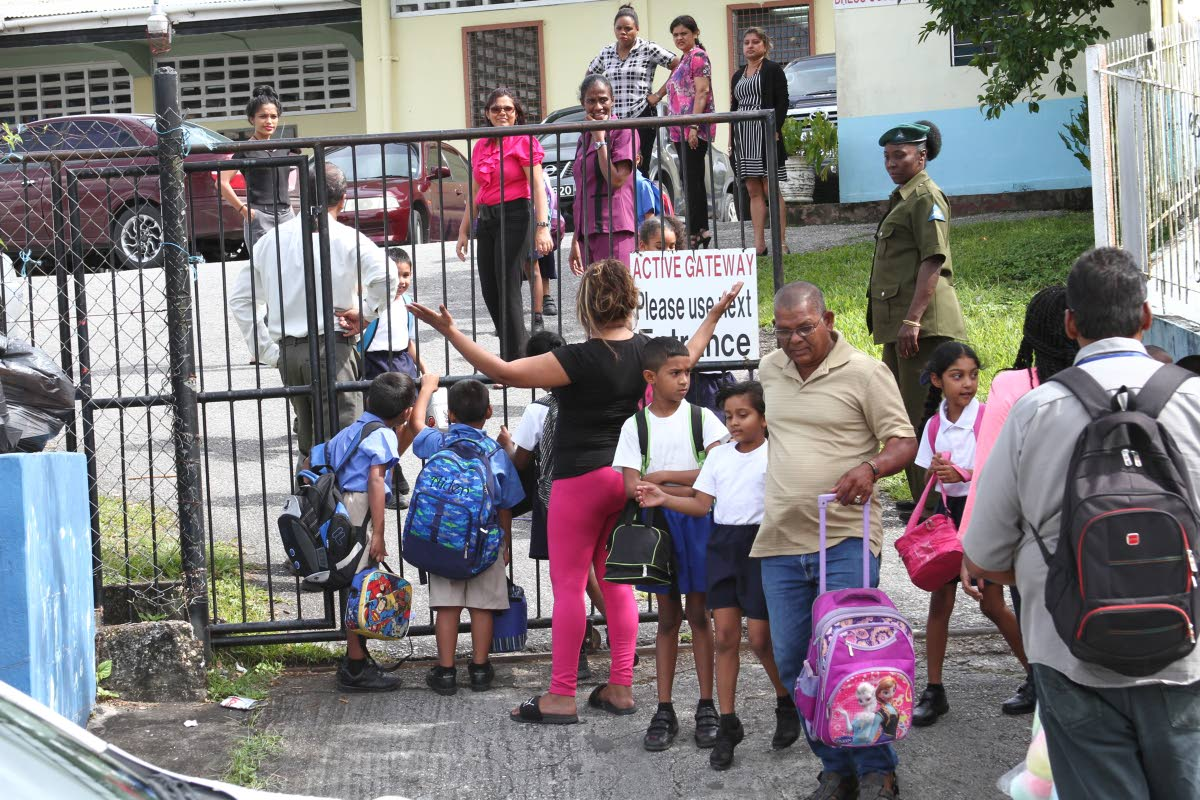 SCHOOL AS NORMAL: Parents collect their children yesterday outside the Jordan Hill Presbyterian Primary school in Princes Town, a day after a teacher was robbed at gunpoint of her van.