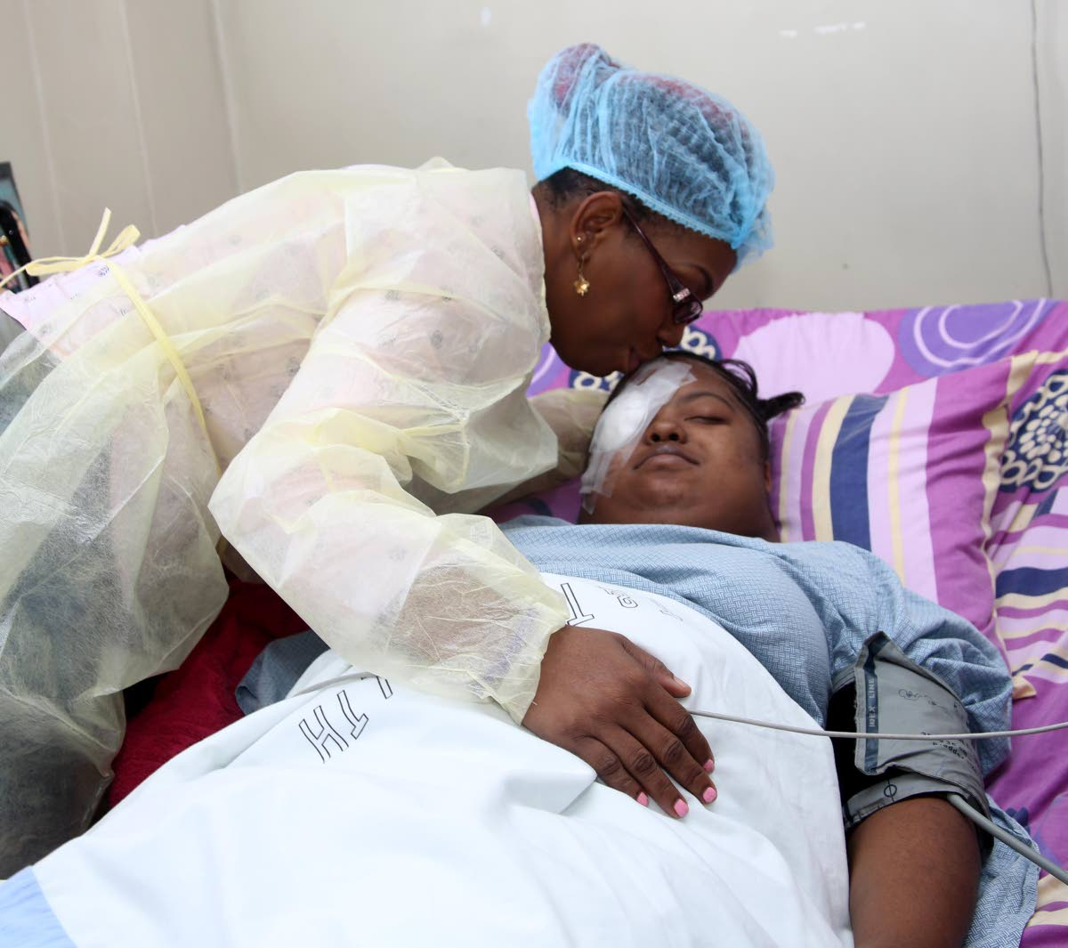 Brenda Henry kisses her daughter Faith Haynes after successful cornea replacement surgery yesterday at the San Fernando General Hospital.