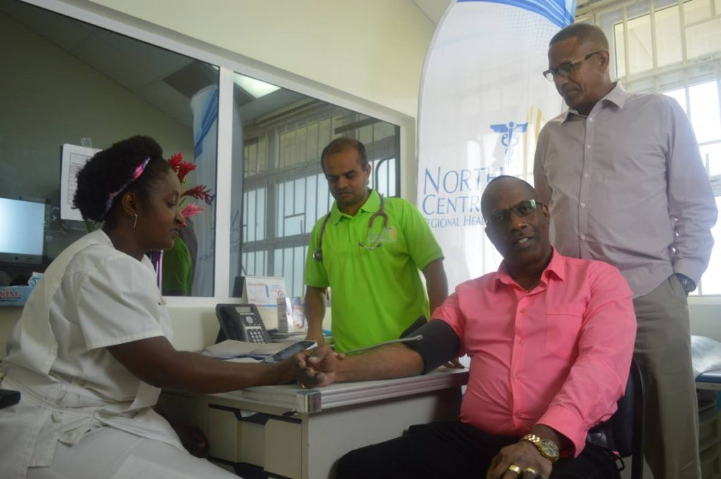 Medical check-up: Nurse Auldith Cato measures the blood pressure of Prisons Commissioner Gerard Wilson at the launch of My Brother's Keeper at the St Joseph Enhanced Health Facility, Mt Hope. Looking on is NCRHA general manager primary care Dr Abdul Hamid, left, and NCRHA chairman Steve De Las. PHOTO COURTESY NCRHA.